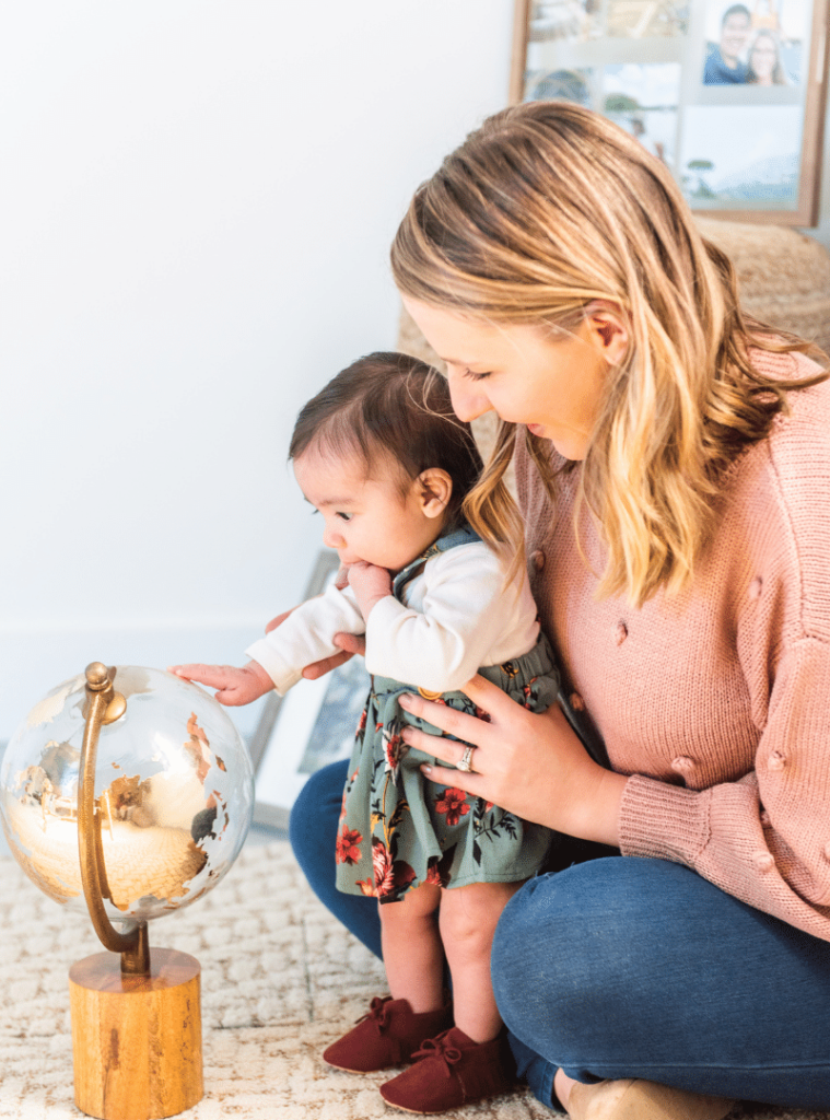 Ashley Triggiano and baby looking at globe