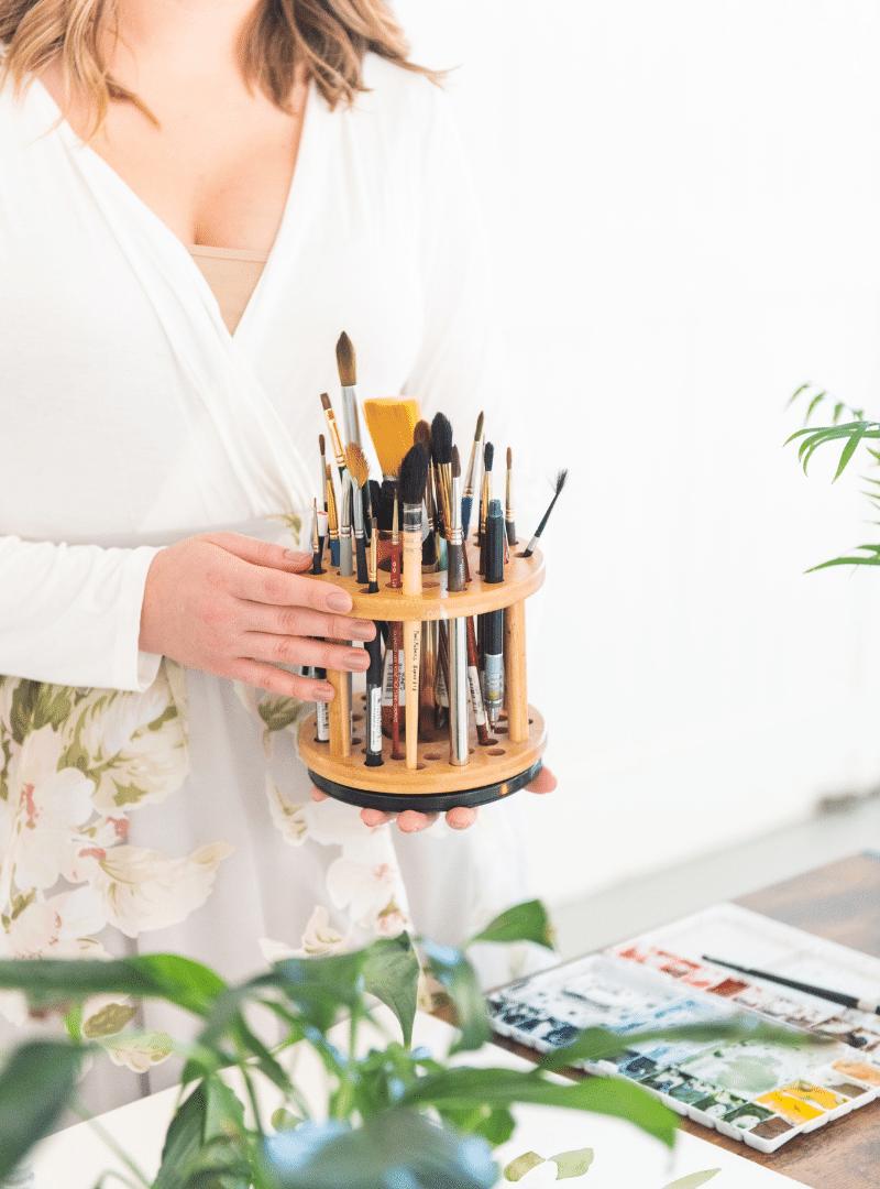 watercolor artist holding paintbrush holder in studio