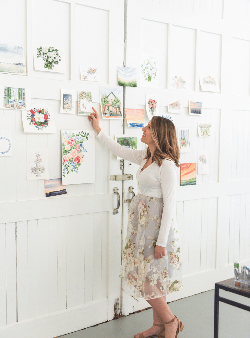 Watercolor artist admires work hanging on white wall