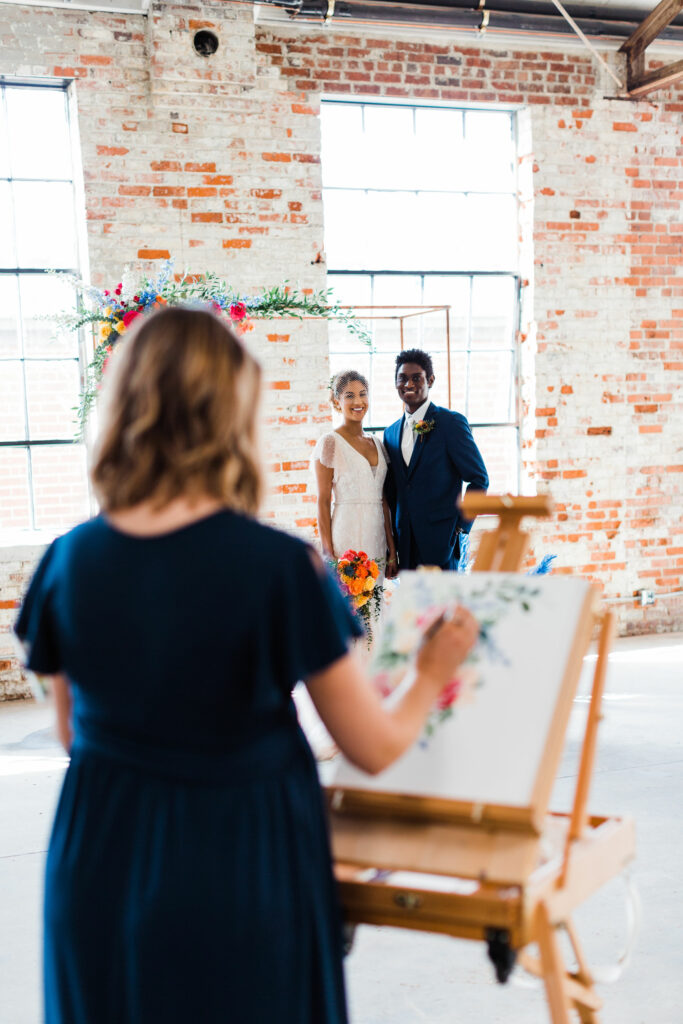 couple stand for live painting at wedding